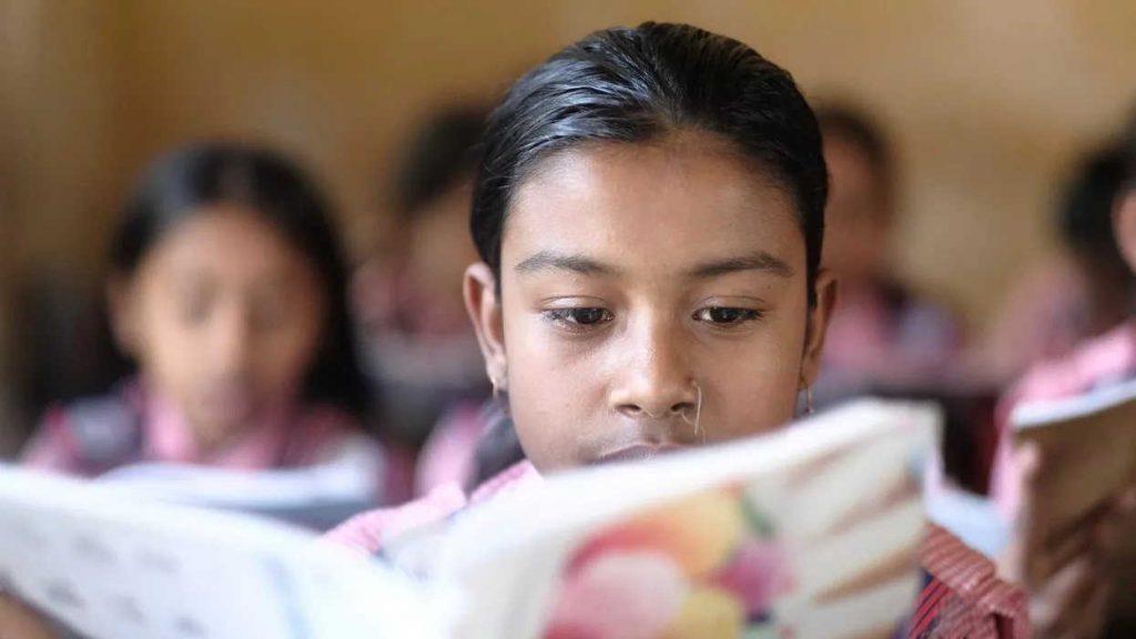 Portrait Of Smiling Girl Reading Book At School In Dhaka Bangladesh