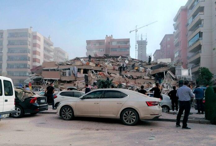 Ciudadanos y personal de rescate intentan llegar hasta personas atrapadas bajo los escombros de un complejo de apartamentos que cayó en Esmirna, Turquía. (The Associated Press)